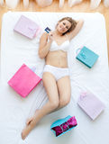 Nice woman lying in bed with shopping bags Stock Image