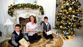 Nice woman and mother and children with boys look and smile at camera with gifts in their hands in good mood and sit on. Happy mother and beautiful woman posing stock footage