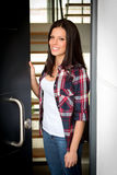 Nice woman opening the door of her house Royalty Free Stock Photo