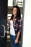 Nice woman opening the door of her house Royalty Free Stock Images