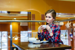 Nice woman in a plaid shirt drinking tea in a cafe Royalty Free Stock Photo