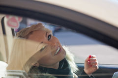 Nice woman smiling you from her car Stock Photography