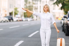 Nice woman standing near road. Waiting for car pull. Pleasant positive attractive woman holding her suitcase and keeping hand up while waving down Stock Image
