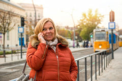 Nice woman on the street. A nice middle age woman standing at a tram station in a winter jacket and speaking on her smartphoner Royalty Free Stock Photo