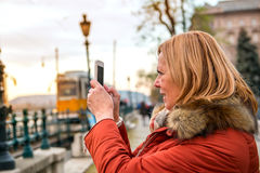 Nice woman on the street with a phone. A nice middle age woman standing and taking photos of the sunset with her phone in the cityr Royalty Free Stock Image
