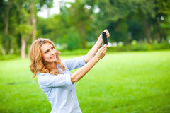 Nice woman taking pictures with smartphone Stock Image
