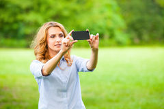 Nice woman taking pictures with smartphone Stock Photo