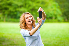 Nice woman taking pictures with smartphone Stock Photography