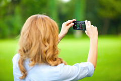 Nice woman taking pictures with smartphone Royalty Free Stock Image