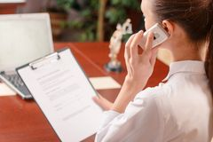 Nice woman talking on phone at work Stock Photo