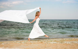 Nice woman in white dress, jumps. Slim woman runs an jumps at the shore Stock Images