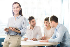 Nice woman working in the office. Real workaholic. Nice attractive women leaning on the table and holding tablet while her colleagues discussing project sitting Royalty Free Stock Photos