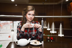 Nice women in a plaid shirt drinking tea in a cafe Royalty Free Stock Photography