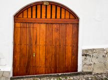 Nice wooden double gate with small arch and. Integrated entrance door on white concrete building Stock Photography