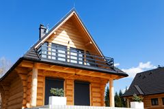 Nice wooden house with a balcony, on a hill under a blue sky. Nice wooden house with a balcony on a hill under a blue sky Stock Photo