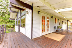 Nice wooden porch with brown trim, white glass doors and metal c Stock Images