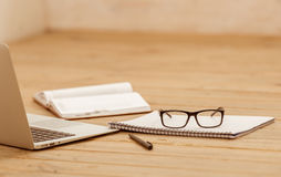 Nice working place. Laptop, eyeglasses and some office supplies on wooden surface Stock Image