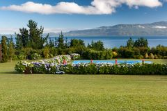 Nice yard with pool and lake view. Grass, flowers, mountains, sunny day some clouds Stock Photos