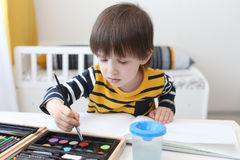 Nice 3 years boy paints with color Royalty Free Stock Image