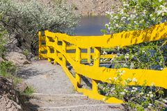 A nice yellow fence along the steps against the backdrop of lake in royalty free stock photo