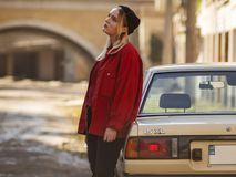 Nice young blonde hipster is standing near the old car on the street stock photo