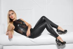 Nice young blonde. Posing in the studio dressed in a black leather suit royalty free stock images