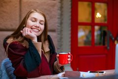 A nice girl sitting in a cafe, holding a mug with a drink and smiling pleasantly with her eyes closed. A nice young brunette girl sitting in a cafe hiding Stock Photography