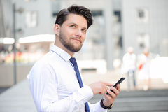 Nice young businessman holding mobile phone. Just dreaming.  Positive handsome bearded businessman holding mobile phone and looking while while going to make a Royalty Free Stock Images