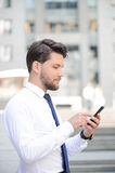 Nice young businessman holding mobile phone. Make a call. Pleasant young bearded businessman holding mobile phone and touching screen while standing half faced Stock Images