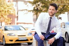 Nice young businessman sitting on stone Royalty Free Stock Images