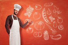 A nice young chef in a chef hat and apron making a presenting gesture at an image of fruit and vegetables on a wall. stock photography