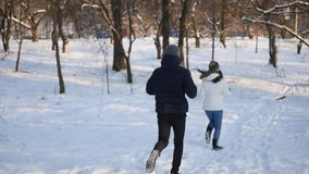 Nice young couple running in the winter forest.  stock video