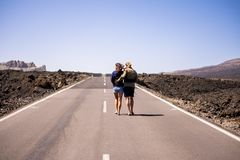 Nice young couple viewed from rear walking together hugging on a long way road in the middle of the lava desert on an asphalt road royalty free stock image