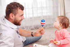 Nice young father holding rattle Royalty Free Stock Photography