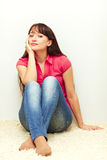 Nice young female sitting relaxed by the wall Stock Image