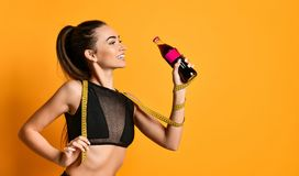 Cute young fitness girl in black suit looks into the camera and keep the measuring tape and bottle at hand stock photo