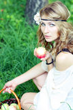 Nice young girl with fresh red apple in the summer park. Nice young girl in wreath with fresh red apple in the summer park Royalty Free Stock Images