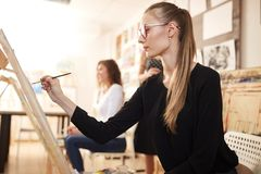 Nice young girl in glasses dressed in black blouse and jeans sits at the easel and paints a picture in the drawing stock image