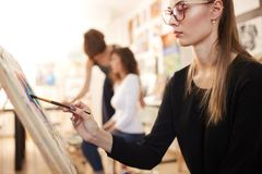 Nice young girl in glasses dressed in black blouse and jeans sits at the easel and paints a picture in the drawing royalty free stock photography