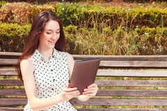 Nice young girl holding laptop. It is time to surf worldwide network. Waist up of pleasant smiling girl holding laptop and surfing  the Internet while sitting on Royalty Free Stock Photo