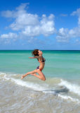 Nice young girl is jumping close to ocean Royalty Free Stock Photos