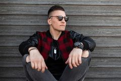 Nice young hipster man in dark sunglasses with a stylish hairstyle in a trendy plaid jacket in gray ripped jeans sits outdoors. Near a wooden building on a stock photo