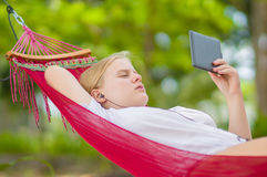 Nice young lady listen music and read book on e-ink reader in  h Royalty Free Stock Image