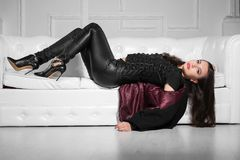 Nice young lady. Posing in studio lying on a white sofa and wearing black clothes royalty free stock photography
