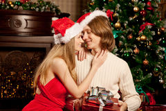Nice young love couple near the Christmas tree. Woman and man ce Royalty Free Stock Photos