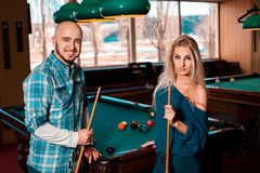 Nice young lovely couple plays billiard and smiling on camera Royalty Free Stock Photo