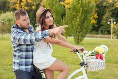 Nice young loving couple is cycling in park Royalty Free Stock Images