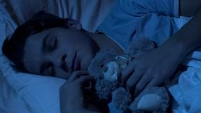 Nice young man cuddling his teddy-bear, sleeping in bed, childhood sweet dreams royalty free stock photos