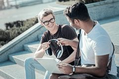 Nice young man giving headphones to his friend. Try them. Nice young delighted men sitting together with his friend and smiling while giving him his headphones Stock Image