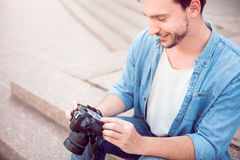 Nice young man holding a camera. Like my work. Cropped image of smiling young man holding a photo camera sitting on steps outdoors Royalty Free Stock Photography